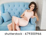 Stock photo a beautiful slender brunette woman in a pink dress with flounces is sitting on a blue velvet 679300966
