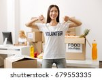 Small photo of Altruistic motivated woman showing off her shirt