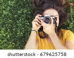smiling young woman using a... | Shutterstock . vector #679625758