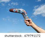 Small photo of SWITZERLAND, 08, JULY 2012: Hand throwing a painted boomerang - the ancient aborigine hunting tool from Australia, nowadays a popular sports.