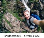 tourist man on a waterfall... | Shutterstock . vector #679811122