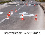 Small photo of Work on the road. Street signs and road marking. Traffic signs for signaling. Road maintenance, under construction sign and traffic cones. Road block with white arrow showing alternate way.