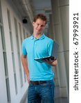 A confident head cocked college guy holds a laptop in a beautiful campus hallway.  Tall handsome male caucasian English model wearing blue shirt looking at camera - stock photo