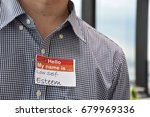 Small photo of A man with a name tag indicating his low self esteem character
