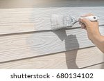 hand of worker painting on wood ... | Shutterstock . vector #680134102