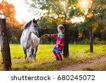 little girl feeding a horse.... | Shutterstock . vector #680245072