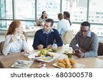Stock photo young business entrepreneurs sitting at breakfast table in office cafeteria 680300578
