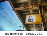 Small photo of A yellow sign of elevator ambiguously tell where to go, with roof and blue sky background.