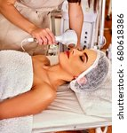 Small photo of Ultrasonic facial treatment on ultrasound face machine. Woman receiving electric lift massage at spa salon. Electronic stimulation female muscles microcurrent therapy . Technologies of rejuvenation.