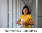 Frustrated female college student in yellow shirt bending abusing her textbook in anger standing in modern university corridor.  20s Asian Thai model of Chinese descent looking at camera - stock photo