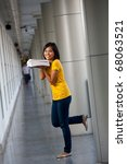 A pretty playful college student wearing yellow t-shirt balances on one leg with her books held near face.  Twenties female Asian Thai model of Chinese descent looking at camera - stock photo