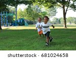 Small photo of Two little boys, one white and the other African American, are running through a park together. Celebrate diversity, racism is taught concept.