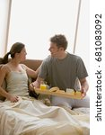 Small photo of Man bringing woman breakfast in bed
