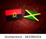 Small photo of Angolan flag with Jamaican flag on a tree stump isolated