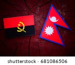 Small photo of Angolan flag with Nepali flag on a tree stump isolated