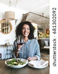 Small photo of Portrait of smiling girl with dark curly hair sitting in restaurant with glass of red wine and salad on table. Beautiful African American lady happily looking aside with glass of wine in hand at cafe