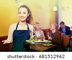 Small photo of Professional friendly smiling nippy with tray posing at table of senior customers