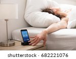 woman turning off the alarm on... | Shutterstock . vector #682221076