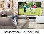 woman lying on couch watching... | Shutterstock . vector #682223452