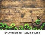 Stock photo st patrick s day horseshoe and shamrock on wooden background 682554355