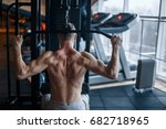 Small photo of Shoulder pull down machine. Fitness man working out lat pulldown training at gym. Upper body strength exercise for the upper back.