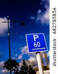 Small photo of P 60 sign (Parking 60 minutes). Blue/white. Sky/trees/street light in background