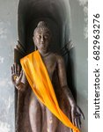 Small photo of Close up picture of old bronze standing Buddha stature in stone chamber
