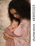 Stock photo beautiful african mother in pink lace dress holding her week old little baby 683052325