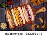 Stock photo hot dogs fully loaded with assorted toppings on a paddle board overhead scene 683358148