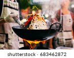man cooks noodles on the fire | Shutterstock . vector #683462872