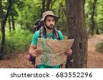 Small photo of Male brunet bearded confused tourist got lost in the forest, holding map, looking far, trying to find the way. He has a backpack, all needed for overnight stay. Search the trail way