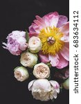 Small photo of Peonies and bombastic roses bouquet. Shabby chic pastel colored wedding bouquet. Closeup view, selective focus