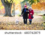 Stock photo senior couple are walking through the autumn woods with their pet dog 683762875