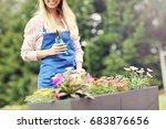 woman growing flowers outside... | Shutterstock . vector #683876656