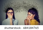 Small photo of Side profile of two preoccupied anxious women looking at each other exchanging with many thoughts