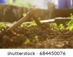 hoe on the ground in the garden | Shutterstock . vector #684450076