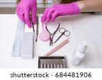 Small photo of Workplace with manicure professional tools on white background. Nailcare instrument in beautician's hands top view