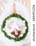 Small photo of An upper sight on a girl lying in a huge green wreath surrounded by burning candles, smiling amicably. She is very happy, top view. Girl lying on back. Beauty and health concept.