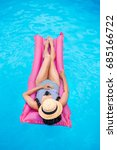 Small photo of Young woman with straw hat covering face floating on air mattress in swimming pool