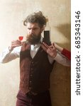 Small photo of Hipster holding glass with red wine and bottle on female hand. Man with long beard, moustache and messy hair on beige wall. Alcohol abuse and alcoholism. Unhealthy lifestyle. Bad habits