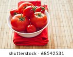 fresh tomatoes on red napkin and bamboo - stock photo