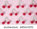 Small photo of lot of Twin Cherry Lollipops like an old time ago on a pink background with blur effect. Minimal color still life photography