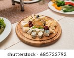 Small photo of Cheese plate with cherries and honey on round wooden board plate on celebratory dinner table, selective focus. Camembert, DorBlu, Emmental, Brie on cutting board