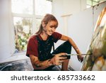 Small photo of Indoor shot of professional female artist painting on canvas in studio. Woman painter painting in her workshop.