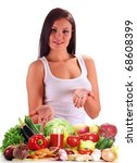 Young woman standing at the table with variety of fresh raw vegetables. Isolated on white. - stock photo
