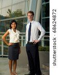 Asian Caucasian business professional workers stand in front of modern glass office building. 20s female Asian Thai of Chinese descent and handsome male British model looking at camera - stock photo