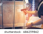 male worker scanning wooden box ... | Shutterstock . vector #686259862