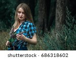 Small photo of A girl with blond hair in a plaid shirt and short denim shorts on a background of trees and nature