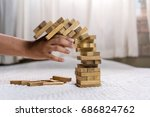 Small photo of Man pulling out wood block fail on building tower at home and drape background
