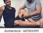 therapist treating injured knee ... | Shutterstock . vector #687001495